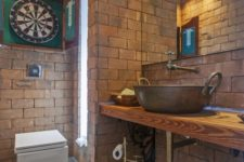 a creative bathroom done with bricks, metal faucets and a sink and a large mirror looks very quirky