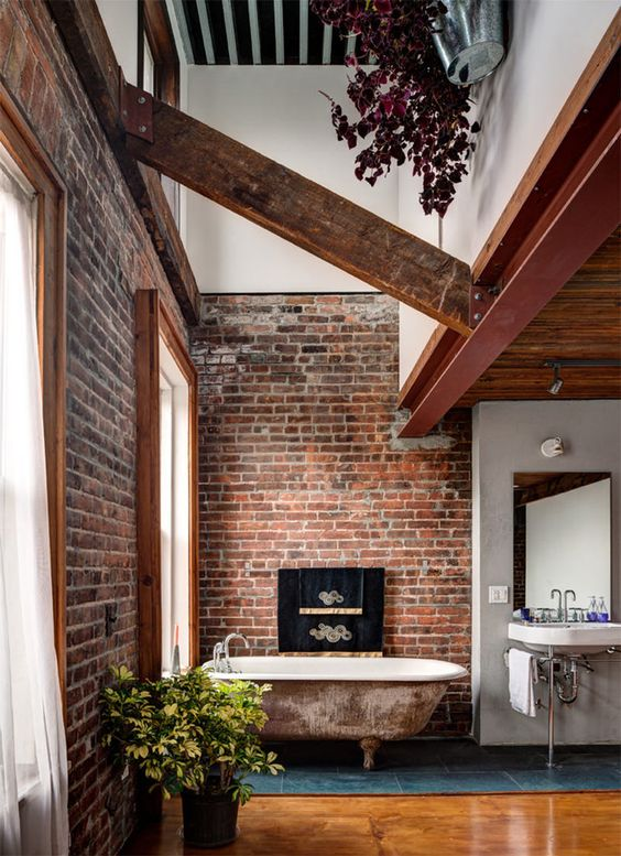 a creative bathroom with red brick walls, wooden beams and an antique bathtub and looks unique