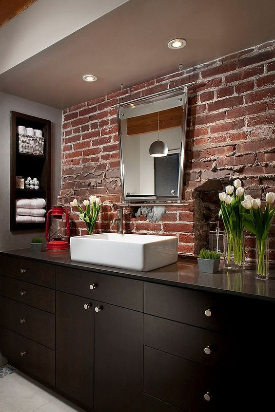 a dark bathroom with a red brick wall and a dark wooden vanity plus built in shelves