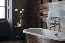 a dark industrial bathroom with red brick walls, dark wooden floora and a chic metal bathtub for a refined look