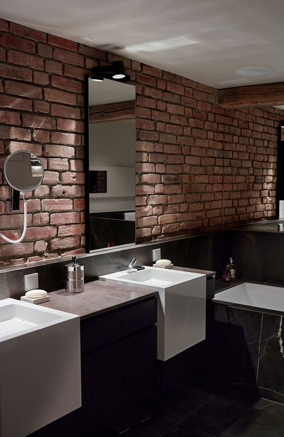 a dark minimalist bathroom with marble tiles, a dark vanity and a red brick wall that adds texture and interest
