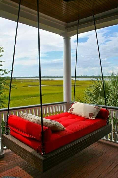 a dark stained wooden hanging bed on ropes with bright bedding and a gorgeous view to enjoy