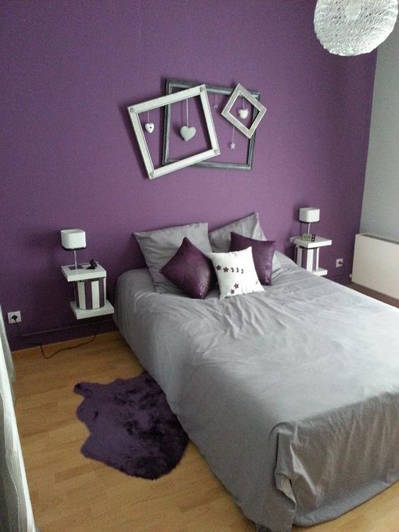 a fun contemporary bedroom with a purple accent wall, a bed, floating nightstands, picture frames and grey and purple bedding