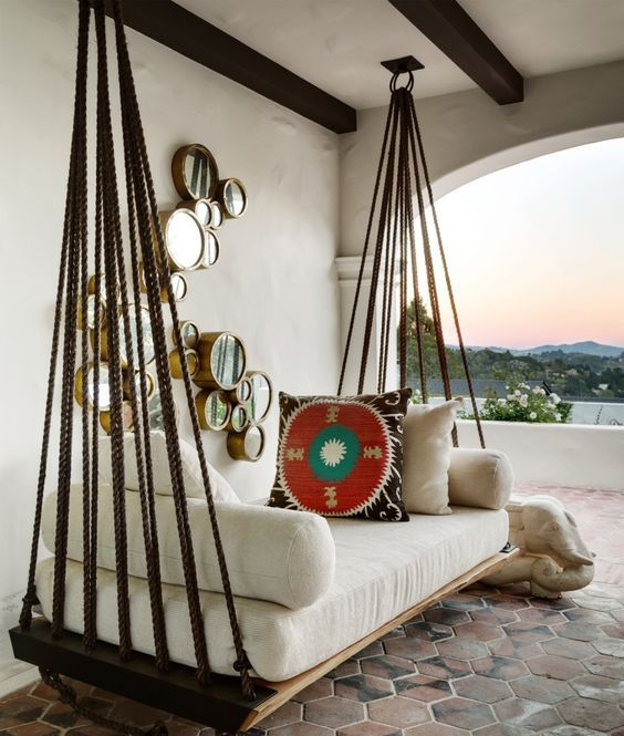 a hanging bed with white cushions and pillows on ropes looks very Mediterranean-like