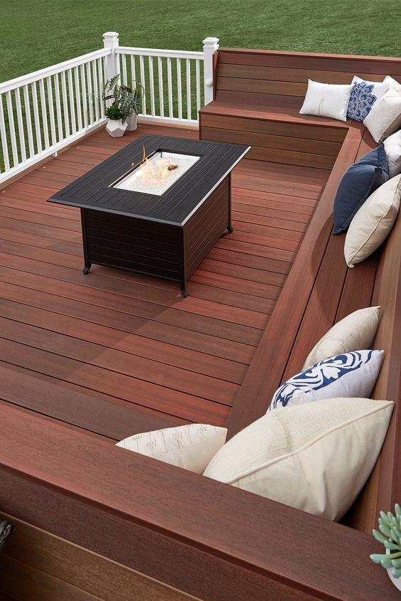a laconic modern deck with a built-in bench, a coffee table with a drink cooler in the center and sculptural planters