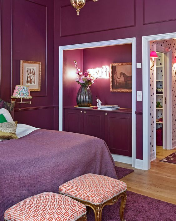a luxurious purple bedroom done with paneling, a bed with purple and white bedding, refined stools and a niche for books
