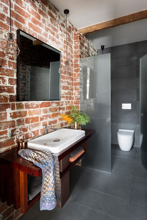 a minimalist bathroom done in greys with a brick wall that adds character and interest to the space