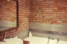 a minimalist meets industrial bathroom with red bricks, grey tiles and a rich-toned vanity