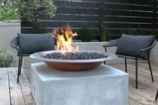 a minimalist summer deck with a concrete cube, a fire pit, dark metal chairs and a screen for privacy