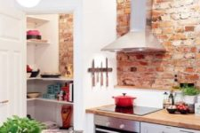 a modern farmhouse kitchen with white cabinets, shiny metal appliances and red brick walls