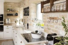 a modern farmhouse kitchen with whitewashed bricks, white cabinets and chic countertops looks very cozy