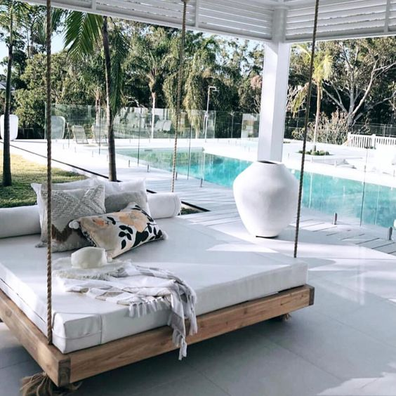 a modern hanging bed on ropes with pillows and blankets is a great idea for an outdoor tropical space
