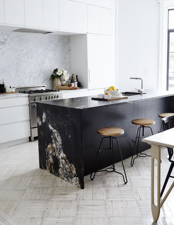 a modern white kitchen and a black kitchen island, a marble backsplash and countertop to tie them up