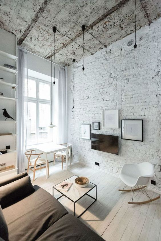 a monochromatic living room with a white brick wall and a rough ceiling for a touch of drama