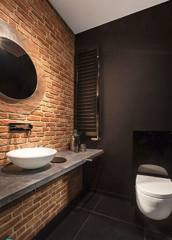 a moody and chic bathroom in black with a single red brick wall that makes the space stand out