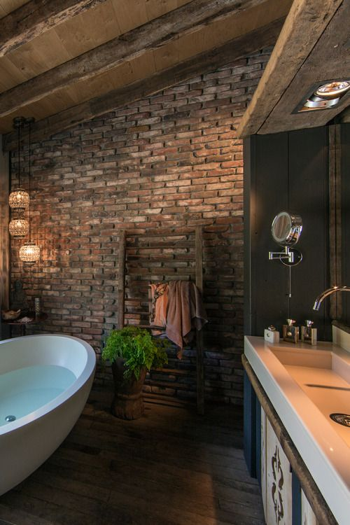 a moody and dark bathroom with brick walls, a wooden floor, large modern fixtures and cool pendant lamps