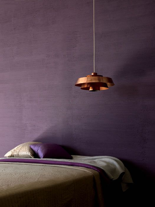 a moody bedroom with a textural purple wall, some purple and grey bedding and a copper pendant lamp over the bed