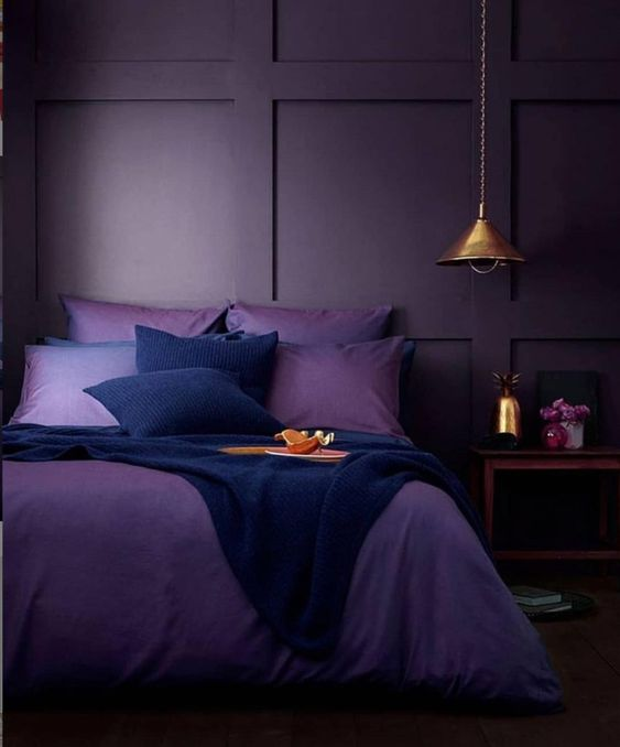 a moody monochromatic bedroom with deep purple paneled walls, purple and navy bedding, a wooden nightstand and a metal pendant lamp