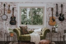 a music nook done with a whitewashed red brick wall and a refined green velvet sofa