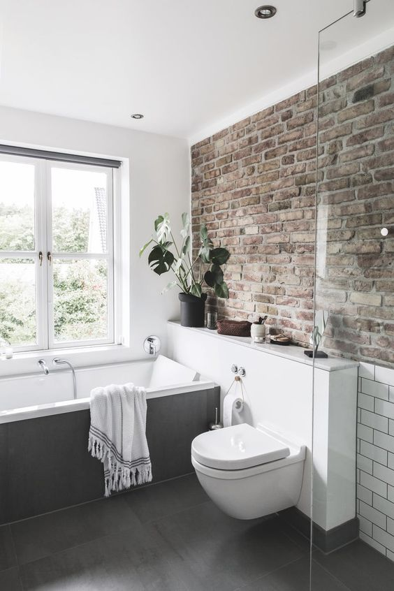 a neutral contemporary bathroom done with a single brick wall that adds character and style to the space