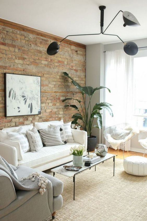 a neutral living room with potted greenery, black touches and an exposed brick wall for more drama