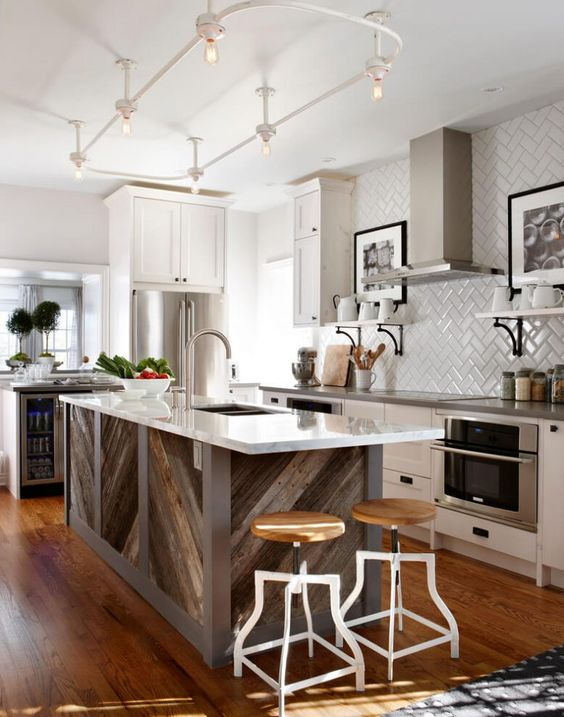 a pallet wood chevron clad kitchen island with a white countertop stands out in this neutral kitchen and adds a rustic feel