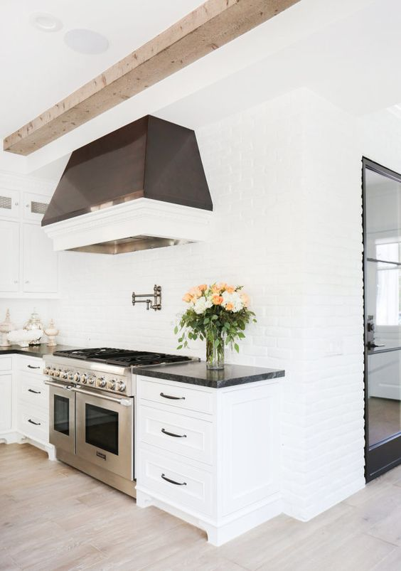 a purely white kitchen with white brick walls and a dark hood that stands out in a neutral space