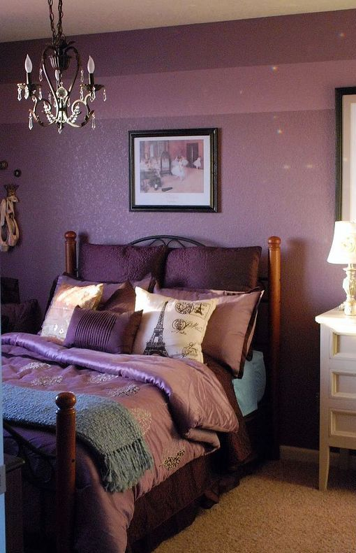 a purple bedroom with a forged bed, purple and pink bedding, a crystal chandelier and some artworks