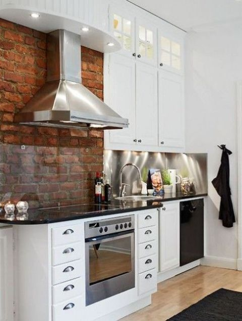 a red brick wall with a backsplash covered with glass to make cleaning more comfortable