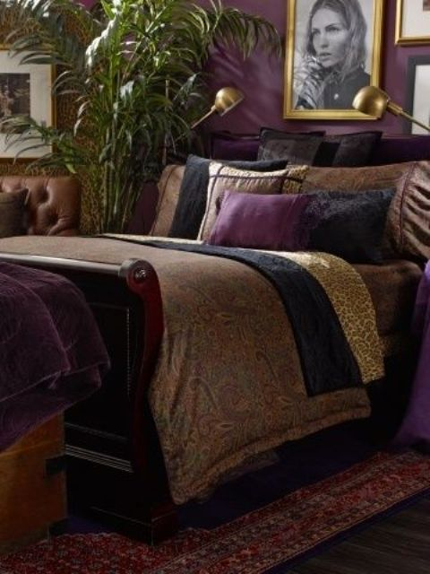 a refined and moody bedroom with purple walls, heavy dark furniture and a gallery wall in gold frames