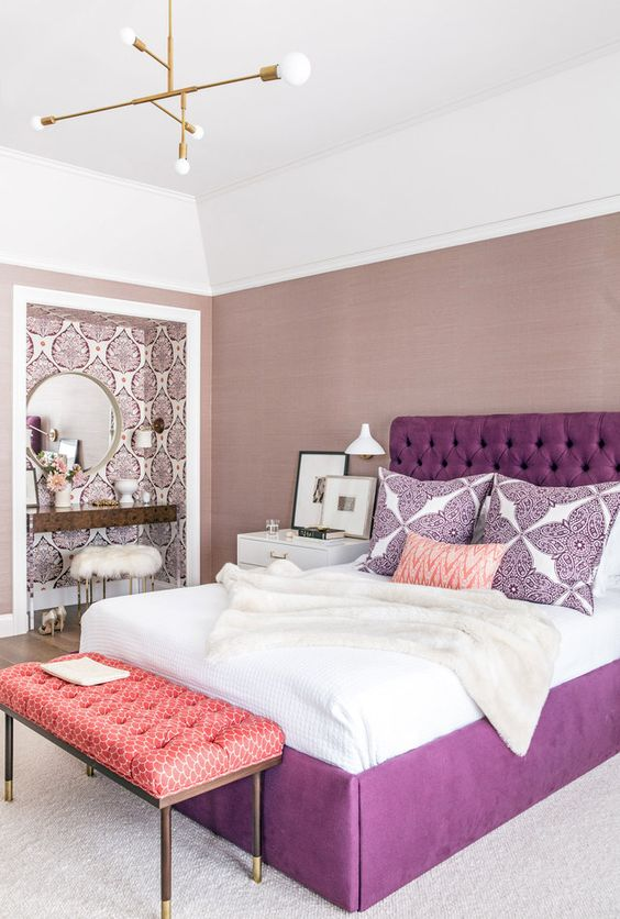 a refined bedroom with mauve walls, a wallpaper makeup niche, a round mirror, a metallic chandelier and a purple bed