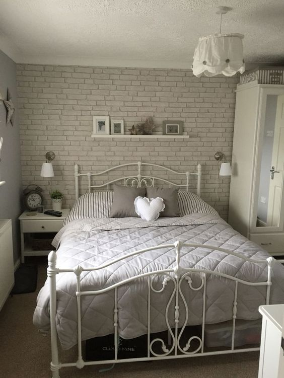 a romantic bedroom with a fau grey brick wall, a forged bed, some chic white furniture and lamps