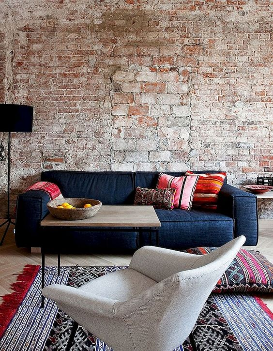 a rough brick wall with bricks of various sizes and colorfuul furniture and rugs to contrast