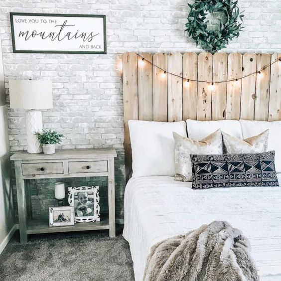 a rustic bedroom with a white fake brick wall, a reclaimed wood bed, lights and vintage furniture