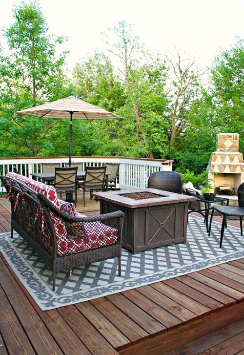 a rustic deck with dark wicker furniture, an umbrella with a dining zone, a fire pit in the center and a fireplace