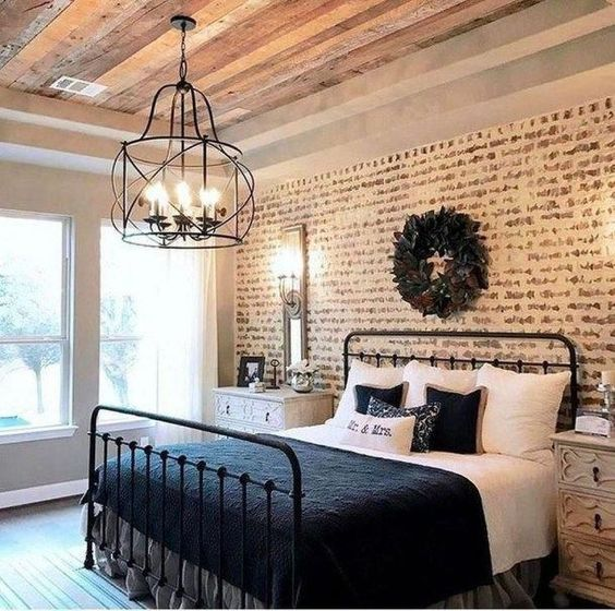 a rustic meets vintage bedroom with a faux brick wall, a forged chandelier and elegant dressers