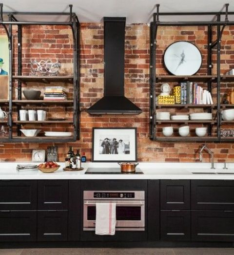 a rustic meets vintage kitchen with a red brick wall, black cabinets and blackened metal shelving units