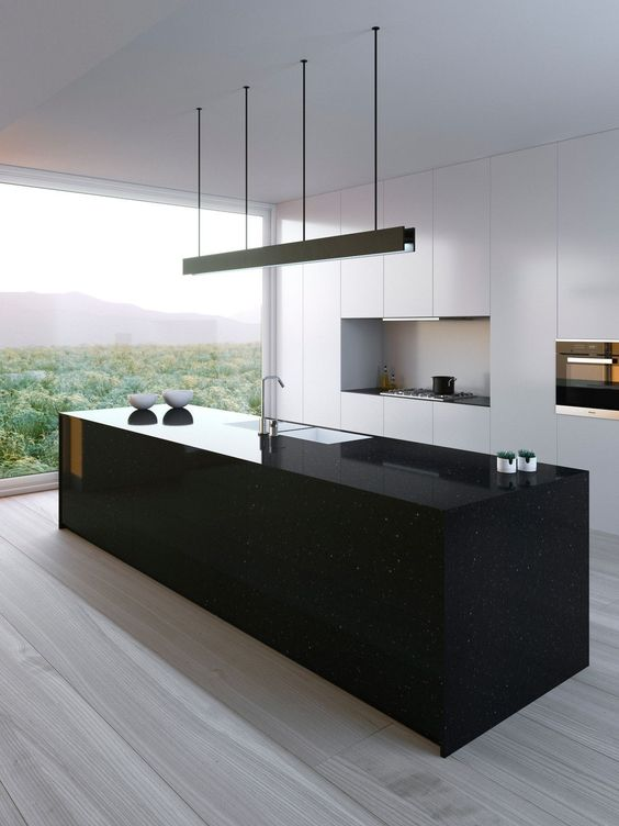 a sleek black kitchen island seems a monolith and contrasts the white kitchen and makes and statement here