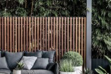 a small contemporary deck with dark stained furniture, potted greenery and succulents, a screen for privacy