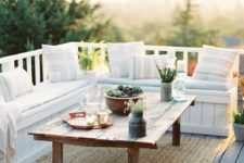 a small deck with a built-in white wooden bench, a rustic coffee table and a jute rug is very welcoming to receive guests