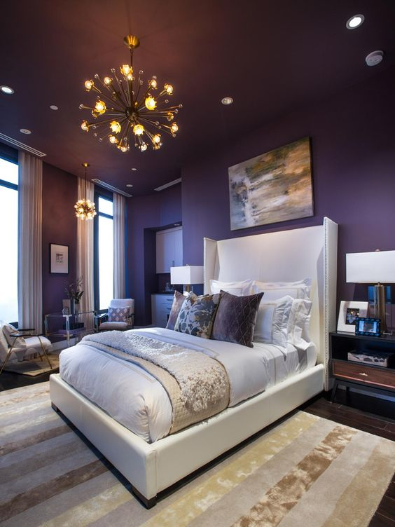 a sophisticated bedroom with deep purple walls, a white bed, stained furniture, sunburst chandeliers and some artworks