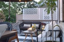 a striped deck with a dining and sitting space, some potted greenery, trees and blooms plus candle lanterns