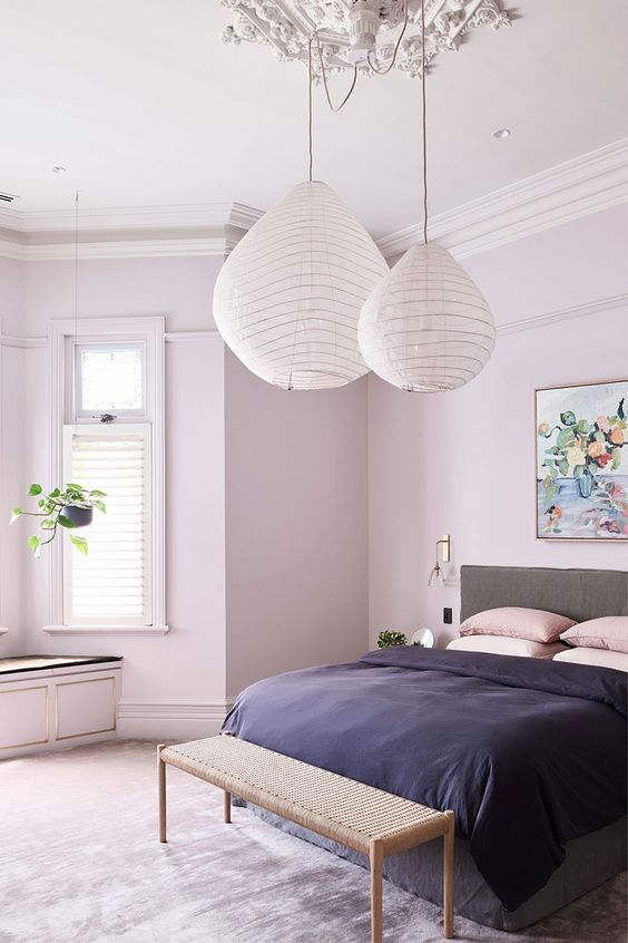 a stylish contemporary bedroom with blush walls, a grey bed, paper pendant lamps and pink and deep purple bedding