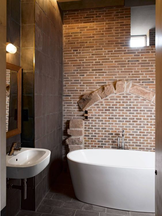 a unique bathroom done with chocolate brown tiles, a red brick wall and white appliances looks really outstanding
