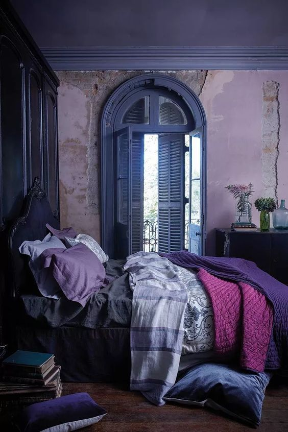 a unique bedroom with lavender walls, a deep purple bed and blue shutters, purple and pink bedding