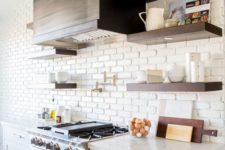 a vintage kitchen with white cabinets, copper hardware and a whiet faux brick wall that makes the hood stand out