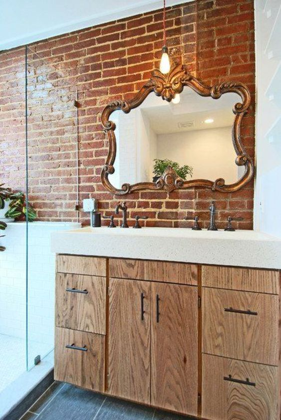 a wall partly done with red brick makes the bathroom more eye-catchy, a bit industrial and cool