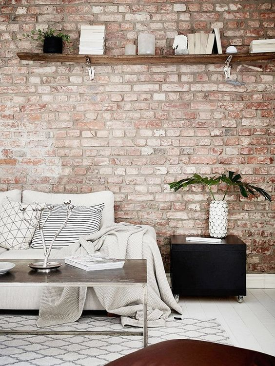 a welcoming living room with a muted red brick wall, neutral furniture and black touches