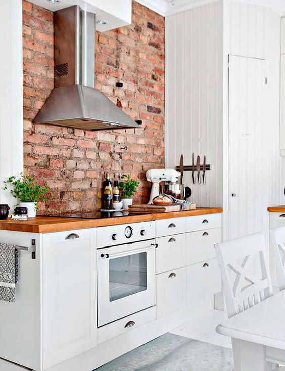 a welcoming modern farmhouse kitchen with white cabinets, rich stained countertops and a red brick wall