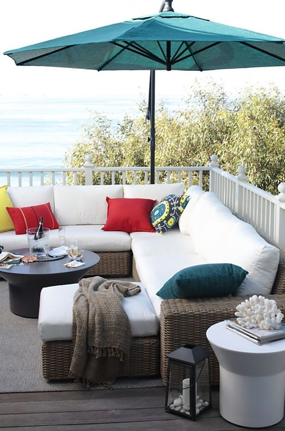 a welcoming summer deck with an L-shaped wicker sofa, a coffee table, some lanterns and a teal umbrella